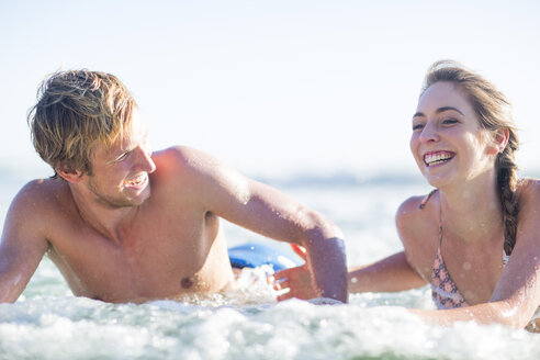 Happy young couple lying on surfboards in the sea - ZEF002403