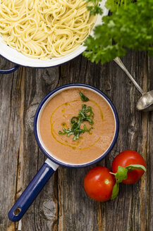 Pot of pasta, saucepan of tomato sauce, tomatoes and basil leaves on wood - ODF000855