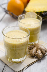 Two glasses of apple pineapple smoothie and ginger root on cloth - ODF000857
