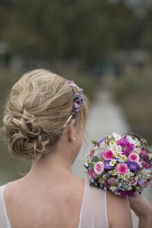 Germany, blond bride with updo and bridal bouquet, back view - HLF000763