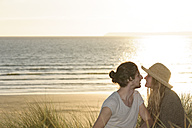 Young couple sitting at beach dunes in front of Atlantic - LAF001178
