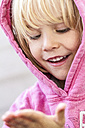 Portrait of smiling little girl watching something on the hand - JFEF000517