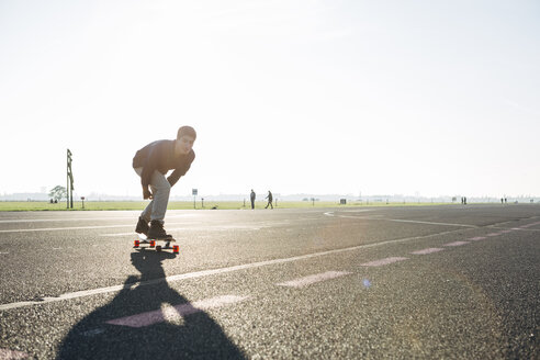 Germany, Berlin, Tempelhof Field, young man skating with longboards - FX000093