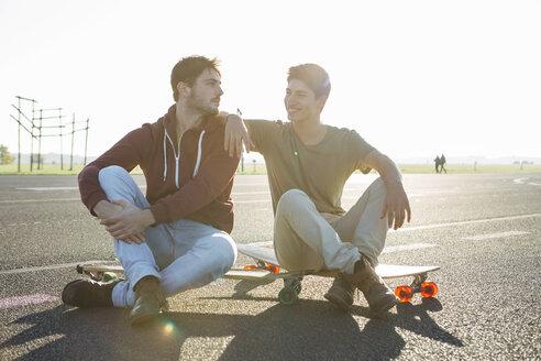 Germany, Berlin, Tempelhof Field, two best friends sitting with longboards on runway - FX000096