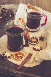 Glasses of mulled wine, orange slices and cinnamon stars on cloth and wooden tray - SARF000984