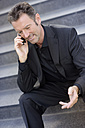 Well dressed businessman sitting on steps telephoning with smartphone - GUFF000038