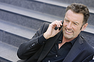 Portrait of smiling businessman sitting on steps telephoning with smartphone - GUFF000041