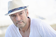Portrait of mature man with stubble wearing summer hat - GUFF000049