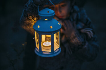 Italy, Grosseto, boy looking at a lighted Christmas lantern by night - BEBF000012
