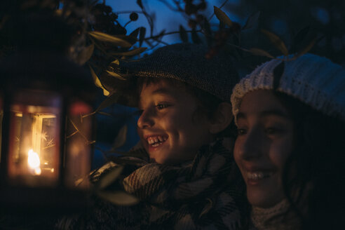 Italy, Grosseto, laughing siblings with lighted Christmas lantern by night - BEBF000015