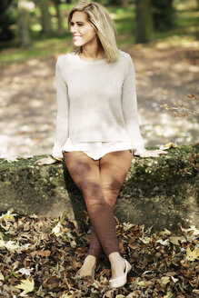 Smiling blond woman wearing knit pullover sitting on a wall - GDF000537