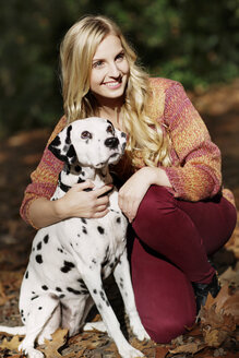 Portrait of smiling blond woman with Dalmatian in autumnal forest - GDF000542
