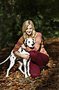 Smiling blond woman with Dalmatian in autumnal forest - GDF000543