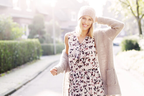 Portrait of smiling blond woman wearing patterned dress, cardigan and wool cap - GDF000549
