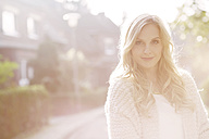 Portrait of smiling blond woman at backlight - GDF000562