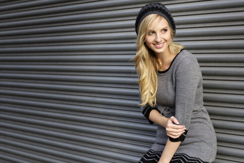 Smiling blond woman wearing knit dress and comforter standing in front of roller shutter - GDF000565