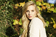 Portrait of blond woman in front of autumn leaves - GDF000566