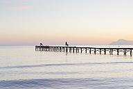 Spain, Balearic Islands, Majorca, people walking on a jetty in the morning light - MSF004332