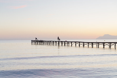 Spain, Balearic Islands, Majorca, people walking on a jetty in the morning light - MSF004332