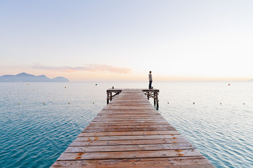 Spain, Balearic Islands, Majorca, one teenage boy standing on jetty in the morning - MSF004344