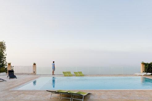 Spain, Balearic Islands, Majorca, one teenage boy standing on a safty glass rail at a swimmingpool - MSF004372