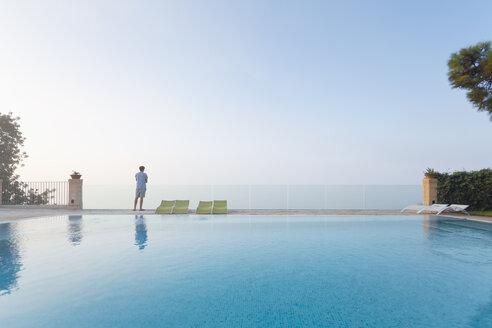 Spain, Balearic Islands, Majorca, one teenage boy standing on a safty glass rail at a swimmingpool - MSF004374