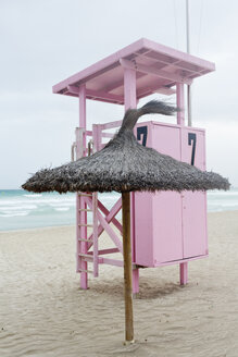 Spain, Balearic Islands, Majorca, lifeguard stand and straw beach umbrella - MSF004362