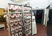 Woman in a butchery pulling rack with sausages for curing - LYF000340