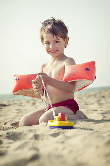 Smiling little boy sitting on the beach with water wings and toy boat - MVC000139