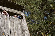 Boy and girl in tree house looking at distance - OJF000075
