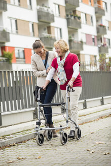 Adult granddaughter assisting her grandmother walking with wheeled walker - UUF002532
