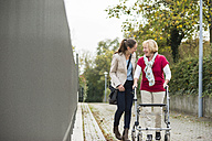Adult granddaughter assisting her grandmother walking with wheeled walker - UUF002534