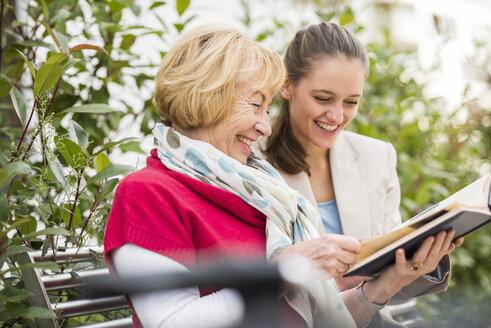 Granddaughter and her grandmother watching photo album - UUF002556
