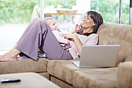 Mother sitting with baby on couch talking on cell phone - ZEF002284