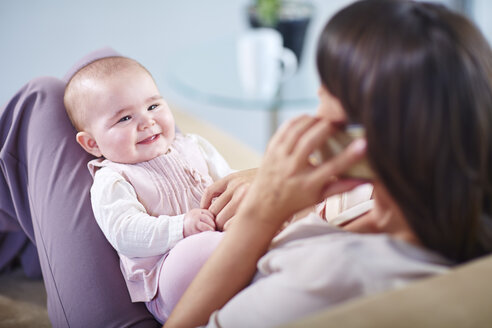 Mother with baby on couch talking on cell phone - ZEF002285