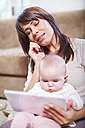 Mother sitting with baby on couch using digital tablet and talking on cell phone - ZEF002291