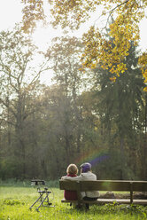 Senior woman and granddaughter sitting on a park bench, back view - UUF002625