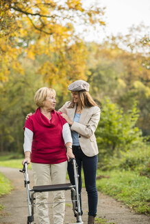 Senior woman and her adult granddaughter walking together in autumnal park - UUF002586