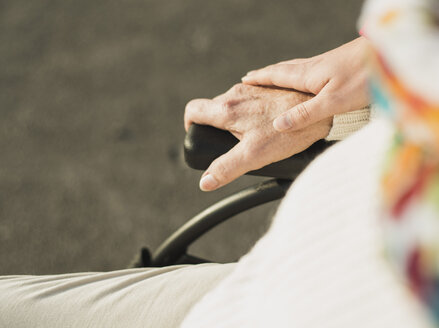 Young woman's hand on hand of senior woman sitting in wheelchair - UUF002593
