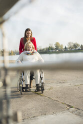 Granddaughter assisting her grandmother sitting in wheelchair - UUF002598