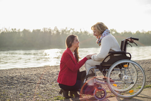 Granddaughter assisting her grandmother sitting in wheelchair - UUF002603