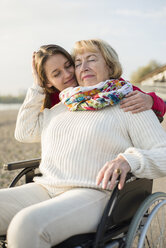 Young woman head to head with her grandmother sitting in wheelchair - UUF002611