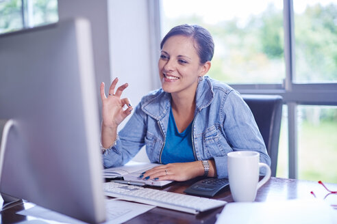 Smiling woman working at desk - ZEF002313