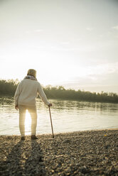 Senior woman with walking stick standing at waterside watching sunset, back view - UUF002613