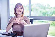 Portrait of smiling woman at desk with laptop - ZEF002317