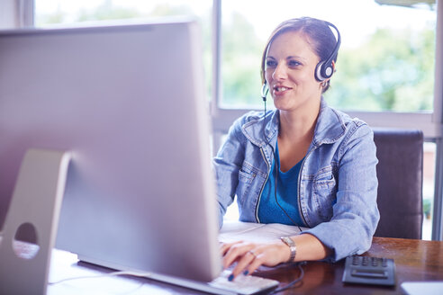 Woman at desk wearing a headset - ZEF002320