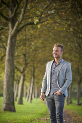 Smiling young businessman standing in a park - PAF001072