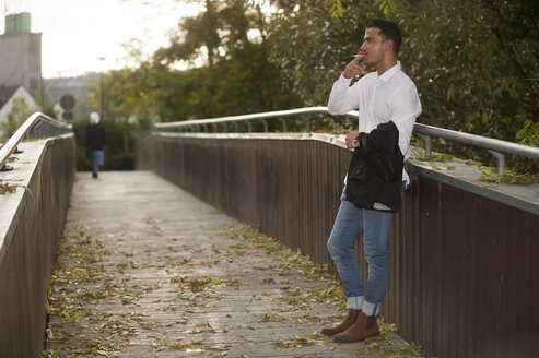Stylish young man smoking a cigarette on a footbridge - PAF001082