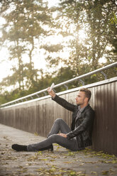 Young man sitting on a footbridge taking a selfie with his smartphone - PAF001083