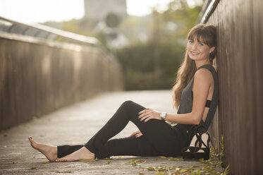 Smiling young woman relaxing on a footbridge - PAF001085